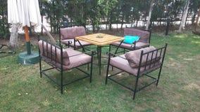 Gartentisch mit Eisenstühlen und -sonnenschirmen Lizenzfreie Stockfotografie