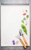 Gartenwerkzeuge mit Blumen und dem Blumenblatt auf leerem Notizbuch Lizenzfreie Stockfotos