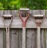 Gartenwerkzeuggriffe, die an einem Bretterzaun hängen Stockfotografie