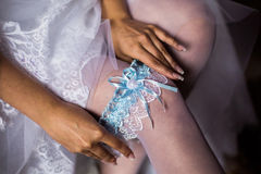 Garter. Blue garter on leg of the bride morning bride, the bride wears a garter on the leg, the preparations for the wedding Royalty Free Stock Photos