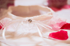 Garter. Delicate garter in rose petals Royalty Free Stock Photography