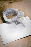 Garter and envelope. Bride's garter lying next to envelope with pencil drawn heart Stock Photos