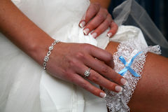 Garter Jewelry. Bride putting garter on leg Royalty Free Stock Photos
