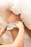 Garter on leg of bride. Hands of person putting garter on leg of young bride in traditional white wedding dress Royalty Free Stock Photo