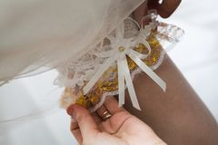 Garter on the leg of a bride. Help the bride dress and white stockings Stock Photography