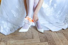 The bride putting on garter. Garter on the leg of a bride, slim sexy bride in wedding luxury dress showing her silk garter. woman have a final preparation for Stock Image