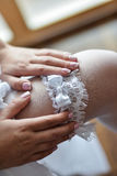 Garter on the leg of a bride, Wedding day moments Royalty Free Stock Photo