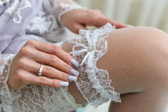 Garter on the leg of a bride, Wedding day moments. Garter on the leg of a bride, slim sexy bride in wedding luxury dress showing her silk garter with golden Stock Photos