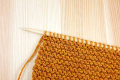 Garter stitch in orange yarn on a knitting needle Royalty Free Stock Photo