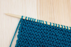 Garter stitch in teal yarn on knitting needle. Length of garter stitch in blue yarn on knitting needle, on wooden background Stock Photography