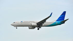 Garuda Indonesia Boeing 737-800 que aterriza en el aeropuerto de Changi Imagenes de archivo