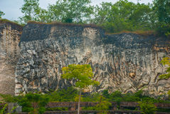 Garuda Wisnu Kencana Cultural Park. Wall of rock on which there is a relief image. Bali. Indonesia. Royalty Free Stock Photography