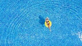Garva i en pöl Kvinnan kopplar av i pölen i solig dag i gul uppblåsbar cirkel arkivfoton
