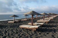Garva sängar och paraplyer på Perissa sätter på land, Santorini, Grekland arkivbild
