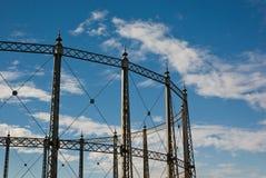 Gasómetro contra un cielo nublado azul imagenes de archivo
