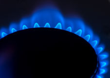 Gas. Natural gas burning blue on a household stove against a black background royalty free stock photos