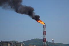 Gas accompagnante bruciante dalla pila della raffineria contro cielo blu Fotografia Stock