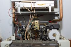Gas boiler repair. On the wall in the room a gas boiler is disassembled for repair stock images