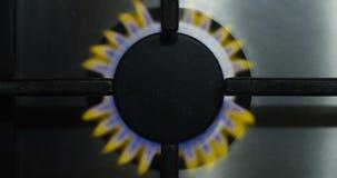 Gas-brennender Ofen mit gelber und blauer Feuer-Flamme im Küchen-Gewindebohrer mit Edelstahl-Oberflächendraufsicht-Schuss auf Rot stock video footage