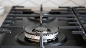 Gas burner on black modern kitchen stove. kitchen gas cooker with burning fire propane gas. / stock image