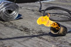 Gas burner with fire and roll of roofing material on blurred background with bokeh effect stock image