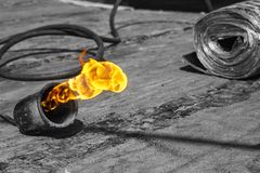 Gas burner with fire and roll of roofing material on blurred background with bokeh effect stock photography