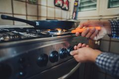 Gas burner with flame on gas cooker. A man lighting the gas-stove with a match royalty free stock photo