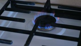 Gas burning from a kitchen gas stove in middle gas burner. Close-up view. stock footage