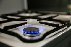 Gas burns on the kitchen stove. Blue flame of gas stove closeup side view. gas stove burner with blue flame. tongue of blue flame stock photography