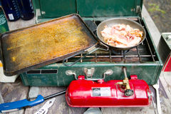 Gas camping stove and sizzling bacon in fry pan. Bacon cooks and sizzles in a frying pan on a gas camping stove Stock Photo