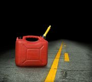 Gas can. A red plastic gas can sits on an asphalt roadway that disappears into the darkness. Concept for running out of gas or fuel stock photos