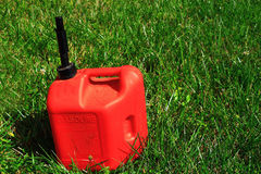 Gas Can. Five gallon non-spill plastic red gas can on green lawn, concept for saving energy to protect environment, green energy stock photos