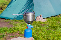 Gas cartridge camping stove and stainless steel pot Royalty Free Stock Photography