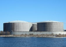 Gas containers at energy plant with lake and blue  Royalty Free Stock Photos