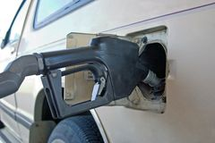 Gas dispenser. A gas pump dispenser filling the gas tank of this vehicle royalty free stock photos