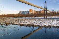 Gas- eller vattenrör över floden och behinen för bostads- byggnader fotografering för bildbyråer