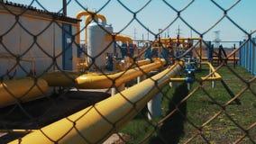 Gas en oliepijpleiding bij de installatie Post voor de verwerking van en het opslaan van aardgas Vervoer van grondstoffen stock videobeelden