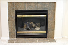 Gas Fireplace. Living room heat producer at the flip of a switch. Surrounded by green brown slate stone Royalty Free Stock Photo