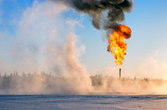 GAS FLARE. Gas flaring. Oil production in Western Siberia. Evaporation of snow stock photo