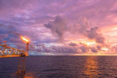 Gas flare is releasing and burning to the atmosphere. At an offshore gas platform with clouds and sky in twilight time Royalty Free Stock Images