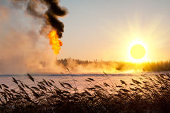 Gas flaring. Flaring of associated gas from oil. Sunrise. Evaporation of snow Stock Photos