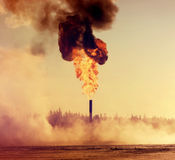 Gas flaring. Gas Torch. Evaporation of snow around huge fire Stock Photos