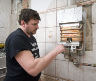 Gas furnace. A gas furnace specialist, plumber man, adjusting it in a newly built bathroom Stock Images