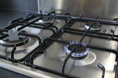 Gas hob. A four ring brushed steel gas hob with focus on the burning ring Royalty Free Stock Image