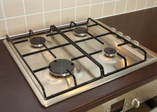 Gas Hob Burner Rings. Modern four-ring gas hob recessed into kitchen worktop over integrated oven below Royalty Free Stock Photo