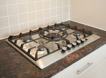 Gas Hob on Granite Worktop. Domestic five-ring gas hob (with central wok burner) on granite work surface. Shallow DoF, focus on centre burner royalty free stock photography