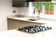 Gas Hob in Kitchen of Empty Residential Property. Narrow DOF with focus on gas hob inset in counter top of modern, empty kitchen in this new house that has royalty free stock photo