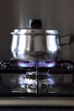 Gas hob and pan. Close up of a gas hob with a pan on the back burner, shallow DOF stock photo