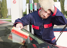 Gas Jockey Cleaning Windshield. Gas Station Worker Cleaning Windshield at Service Station Stock Images