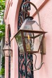 Gas Lantern Porch Lights. Vintage gas lanterns light this iron gate entryway Stock Photo